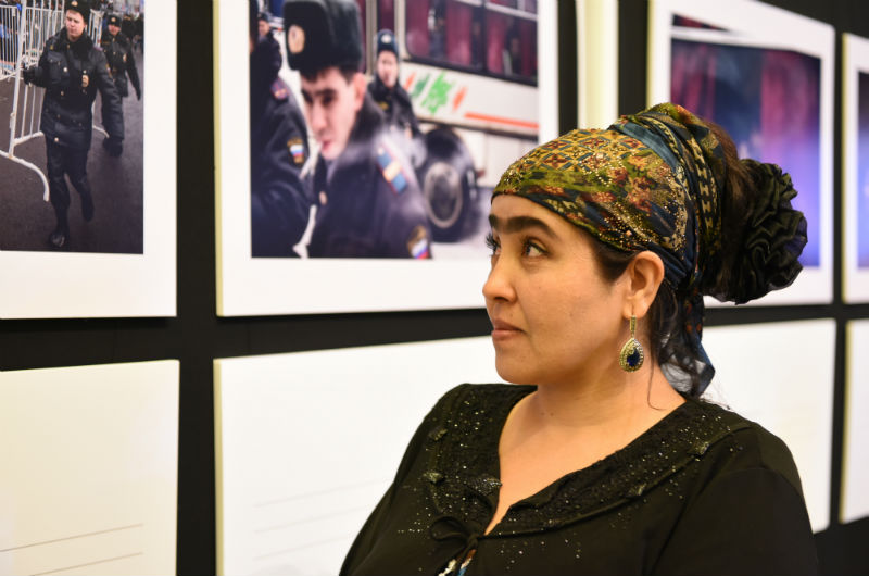 Returned migrant Sadbarg Gazieva looks at pictures in an exhibition on migration at the American University of Central Asia, Kyrgyzstan, during discussions on the Global Compact for Migration in the capital Bishkek. Photo: IOM 2017
